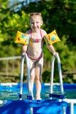 Девушка стоя на шагах бассейна в подушках Стоковая Фотография