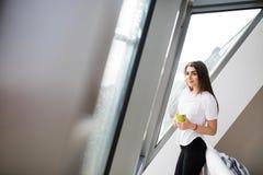 Девушка стоя около больших окна и кофе или чая питья в утре дома Стоковое Изображение