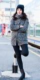 Девушка стоя около железнодорожного вокзала пробуя держать назад ее разрывы, ждать кто-то Стоковое фото RF