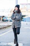 Девушка стоя около железнодорожного вокзала пробуя держать назад ее разрывы, ждать кто-то Стоковая Фотография RF