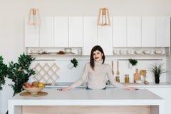 Девушка стоя около кухонного стола Яркая, белая кухня Счастливая усмехаясь девушка в кухне Кухня Стоковое Изображение