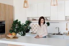Девушка стоя около кухонного стола Яркая, белая кухня Счастливая усмехаясь девушка в кухне Кухня Стоковая Фотография