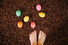 Девушка стоя около пасхальных яя Взгляд сверху, плоское положение Ноги стоковые изображения