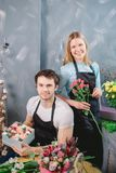 Девушка стоя с пуком и человек сидя на таблице с составом цветков Стоковое Изображение RF