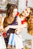 Девушка 2 стоя с сумками в платьях обнимая и смеясь над на моле Концепция счастья, покупки, приятельство Стоковое фото RF