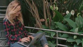 Девушка студента битника работает на компьтер-книжке в зале железнодорожного вокзала сток-видео