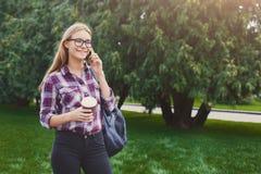 Девушка студента говоря на черни с кофейной чашкой Стоковое Изображение RF