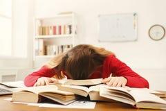 Девушка студента изучая на таблице вполне книг Стоковое Фото