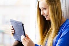 Девушка студента при таблетка сидя на windowsill Стоковая Фотография