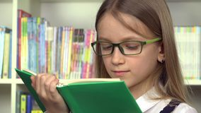 девушка студента 4K, книги чтения стороны ребенка в библиотеке, школьном образовании детей акции видеоматериалы