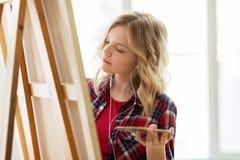 Девушка студента с картиной мольберта на художественном училище Стоковые Фотографии RF