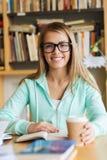 Девушка студента с кофе книги выпивая в библиотеке Стоковое Изображение RF