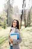 Девушка студента университета смотря счастливый усмехаться с книгой или тетрадью в парке кампуса Кавказская модель женщины молодо Стоковое Изображение RF