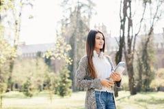 Девушка студента университета смотря счастливый усмехаться с книгой или тетрадью в парке кампуса Кавказская модель женщины молодо Стоковое фото RF