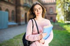 Девушка студента университета смотря счастливый усмехаться с книгой или тетрадью в парке кампуса Стоковые Изображения