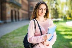 Девушка студента университета смотря счастливый усмехаться с книгой или тетрадью в парке кампуса Стоковые Изображения RF