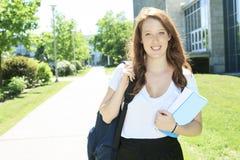 Девушка студента университета смотря счастливый усмехаться с Стоковая Фотография