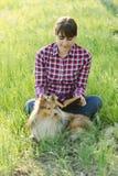 Девушка студента уча в природе с собакой Стоковое фото RF