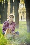 Девушка студента уча в природе с собакой Стоковые Фото