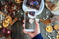 Девушка сфотографировала на таблице smartphone с шоколадом питья горячим Стоковые Фото