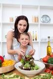 девушка счастливая ее мать подготовляя салат Стоковое фото RF