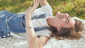 Девушка счастлива потому что она выполнила ее желания Лежать в лете в парке на шотландке merino Посылает воздух видеоматериал