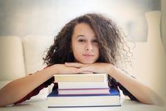 Девушка счастливого вьющиеся волосы предназначенная для подростков отдыхая на книгах Стоковые Фото