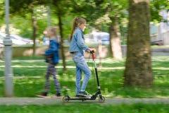 Девушка счастливо едет самокат вдоль дороги асфальта стоковое фото