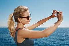 Девушка счастливого selfie фитнеса белокурая усмехаясь и принимая selfe Стоковая Фотография