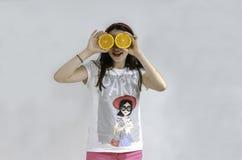 Девушка с апельсинами в ее предпосылке серого цвета глаз стоковое изображение rf