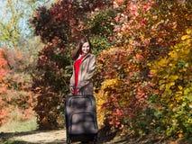 Девушка с багажом на проселочной дороге в лесе стоковое фото