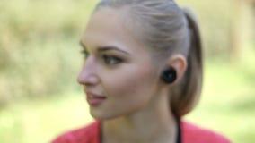 Девушка 2 с беспроволочными наушниками приниманнсяая за физическая культура в парке Преимущества современных технологий