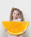 Девушка с большим куском апельсина в ее руках, как концепция для того чтобы достигнуть лучшего и больше в жизни Стоковые Изображения