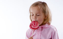 Девушка с большим удовольствием имеет леденец на палочке стоковые изображения rf