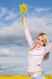 Девушка с букетом желтых цветков против неба Стоковое Фото