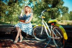 Девушка с букетом цветков около велосипеда Стоковые Фото