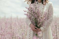 Девушка с букетом цветков шалфея на поле стоковые изображения rf