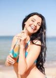 Девушка с бутылкой питья на пляже Стоковые Фотографии RF