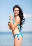 Девушка с бутылкой питья на пляже Стоковая Фотография