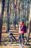 Девушка с велосипедом среди деревьев стоковые изображения rf