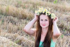 Девушка с венком маргариток в поле Стоковое Изображение RF