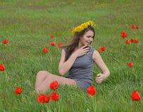 Девушка с венком одуванчиков на ее голове Красивая fairy маленькая девочка в поле среди цветков тюльпанов Стоковые Фотографии RF