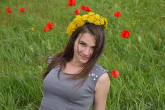 Девушка с венком одуванчиков на ее голове Красивая fairy маленькая девочка в поле среди цветков тюльпанов Стоковая Фотография
