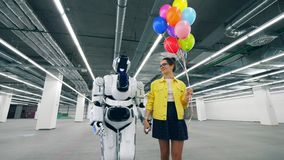 Девушка с воздушными шарами и droid идут в комнату, держа руки сток-видео