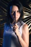 Девушка с волшебным sorcerer& x27 брюнет- палочки; подмастерье s, на предпосылке золота, использует произношение по буквам Стоковая Фотография RF