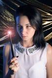 Девушка с волшебным sorcerer& x27 брюнет- палочки; подмастерье s, на предпосылке золота, использует произношение по буквам Стоковое фото RF