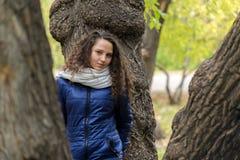 Девушка с вьющиеся волосы на стволе дерева в парке осени Стоковое Фото