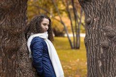 Девушка с вьющиеся волосы на стволе дерева в парке осени Стоковое фото RF