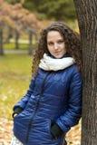 Девушка с вьющиеся волосы на стволе дерева в парке осени Стоковые Фотографии RF