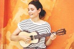 Девушка с гавайской гитарой гитары на предпосылке стены стоковые изображения